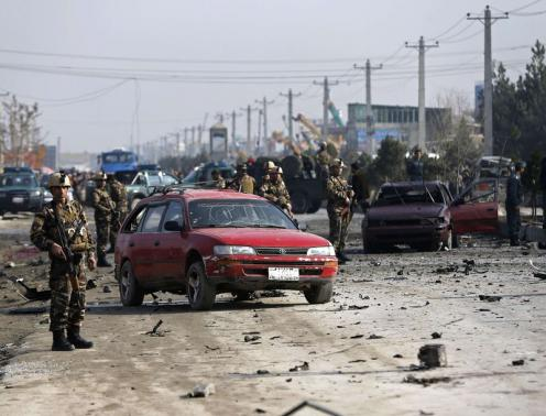 Afghan security forces inspect the site of a suicide attack on a British embassy vehicle in Kabul